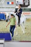 在一套蓝色衣服的女性骑师骑马在一个白马 国际马陈列莫斯科 免版税图库摄影