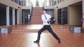 在一套西装的一个年轻愉快的英俊的商人有跳舞现代的芭蕾舞剧的公文包的反对a背景  股票录像