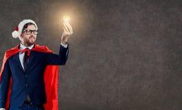 在一套超级英雄圣诞老人服装的一个商人有一个电灯泡的 免版税库存照片