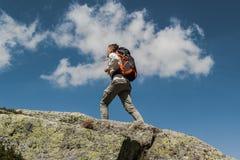在一好日子期间,有大背包的走的年轻人到达山的上面 免版税图库摄影