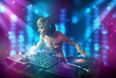 在一家俱乐部的Dj女孩混合的音乐与蓝色和紫色光 图库摄影