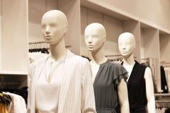 在一家妇女的服装店的时装模特在轻的背景 免版税库存图片