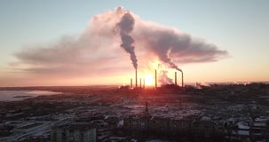 在一家抽烟的工厂的背景的史诗日落 与明亮的光芒的红色太阳超出管子工厂和烟雾范围 影视素材