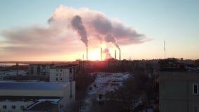 在一家抽烟的工厂的背景的史诗日落 与明亮的光芒的红色太阳超出管子工厂和烟雾范围 股票录像