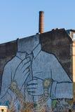在一家老被放弃的工厂的门面的巨型街道画 免版税库存照片