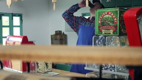 在一家老,减速火箭的商店喝从玻璃的酒的射击一位年轻卖主 股票录像