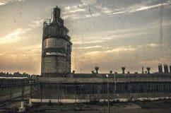 在一家被放弃的工厂破晓,安置与管子,导线和工业 在天空,黎明 库存照片