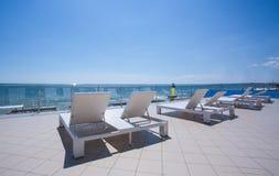 在一家豪华旅馆的阳台的很多白色sunbeds 在热带海滩附近的白色轻便折叠躺椅 katya krasnodar夏天领土假期 免版税库存照片
