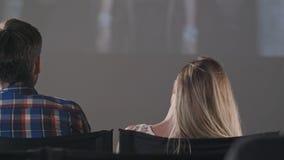 在一家黑暗的电影院观看电影的观众人 图库摄影