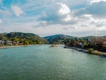在一小镇中间的河有山和多云天空背景的 免版税库存照片