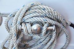 在一层木救生艇甲板盘绕的白色绳索 库存图片