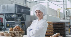 在一工业厨房微笑大和看的照相机吸引人面包师妇女前面离群对照相机 股票视频