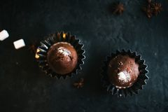 在一幅黑暗的背景静物画的杯形蛋糕 免版税库存图片