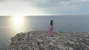 在一年轻女人的鸟瞰图礼服的站立在峭壁边缘 股票视频