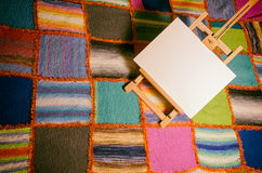 在一床五颜六色的被子前面的绘画画架 库存照片