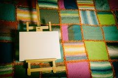 在一床被编织的被子的绘画画架 库存图片