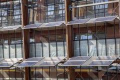 在一座办公楼的前面的太阳电池板作为解答fo 图库摄影