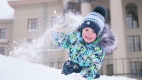 在一座多雪的山的小儿童游戏,投掷下雪和笑 晴朗的冷淡的日 乐趣和比赛在新鲜空气 免版税库存图片