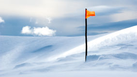 在一座多雪的山顶部的旗子 免版税图库摄影