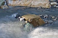 在一座小山的冰砾放出围拢由流动的水很长时间曝光 图库摄影