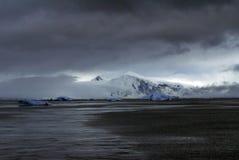 在一座山下的冰山在风雨如磐的天空下 免版税库存图片