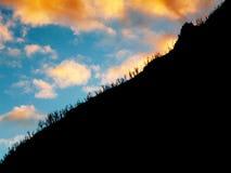 在一座山后的多云日落在安地斯 免版税库存照片