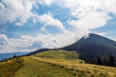 在一座山的上面的云彩与绿色森林和草草甸的 库存图片