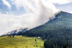 在一座山的上面的云彩与绿色森林和草草甸的 库存照片