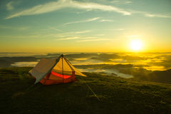 在一座山的上面的帐篷与日出的 免版税库存照片