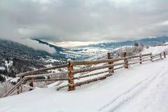 在一座山的冬天风景与在foregr的木篱芭 免版税库存照片