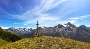 在一座山的十字架在意大利阿尔卑斯前面 库存照片