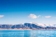 在一座山的天空与由海的雪 免版税库存图片