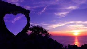 在一座山的心形的石头与紫色天空日落 库存图片