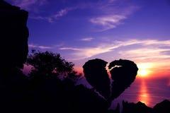 在一座山的残破的心形的石头与紫色天空日落 库存照片