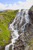 在一座山的瀑布与多云天空 免版税库存照片