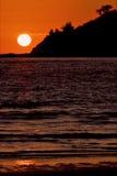 在一座山附近的太阳在海洋 库存图片
