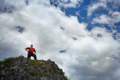 在一座山顶部的一个人反对与云彩的蓝天 免版税库存照片