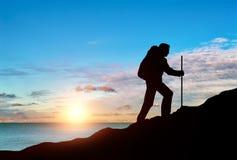 在一座山顶部的上升登山人在海日落背景  免版税库存图片