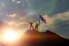 在一座山顶部的夫妇与美国的旗子,日落背景的 免版税库存图片