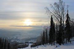 在一座山顶部的日出与滑雪者的,挡雪板倾斜 免版税库存图片