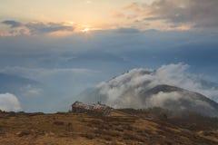 在一座山顶部的老房子在云彩 库存图片
