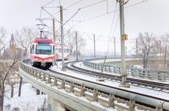 在一座弯曲的桥梁的轻的路轨火车在一个斯诺伊冬日 库存图片