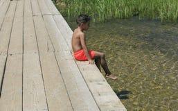在一座木脚桥梁的男孩就座在湖 免版税库存照片