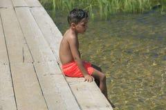 在一座木脚桥梁的男孩就座在湖 图库摄影