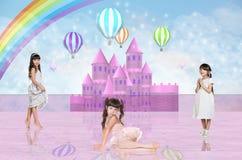 在一座桃红色神仙的城堡前面的三个小女孩 库存图片