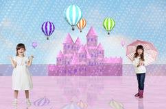 在一座桃红色神仙的城堡前面的两个小女孩 库存图片