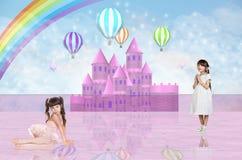 在一座桃红色神仙的城堡前面的两个小女孩 免版税库存图片