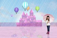 在一座桃红色神仙的城堡前面的小女孩 免版税图库摄影