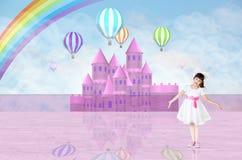 在一座桃红色神仙的城堡前面的小女孩 库存照片