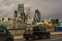 在一座桥梁在伦敦,在a的一辆符号车的黑伦敦出租汽车 库存照片